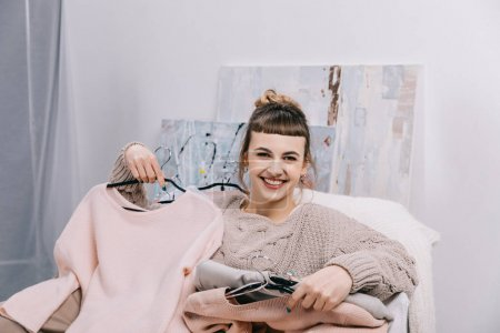 Photo for Smiling girl sitting on armchair with clothes on hangers and looking at camera - Royalty Free Image