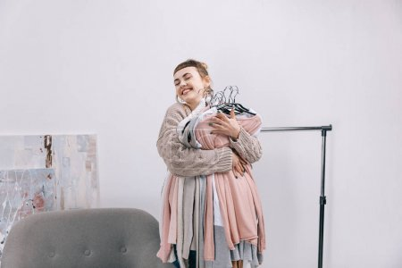 Photo for Happy girl holding stack of clothes on hangers - Royalty Free Image