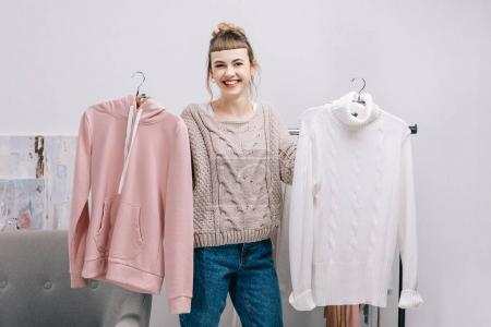 smiling girl standing and holding hangers with sweaters