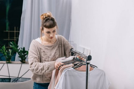 girl standing at stand with clothes and choosing what to wear