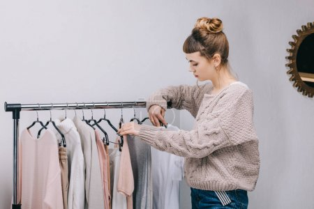 side view of girl standing near stand and choosing what to wear