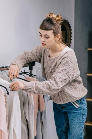 girl standing near stand and choosing what to wear