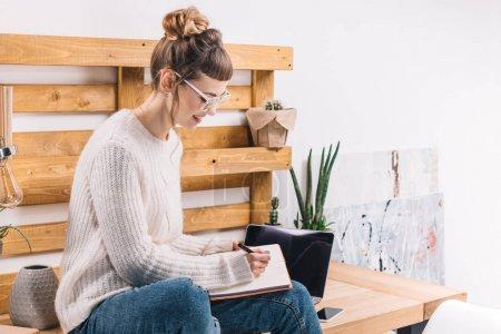 Photo pour Fille souriante assise sur la table dans le bureau et écrire quelque chose pour ordinateur portable - image libre de droit