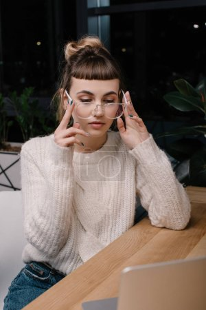 girl wearing glasses and looking at laptop in office