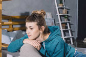 girl sitting on armchair in bedroom and looking away