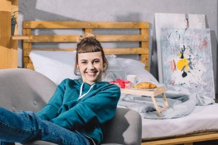 smiling girl sitting on armchair in bedroom and looking at camera