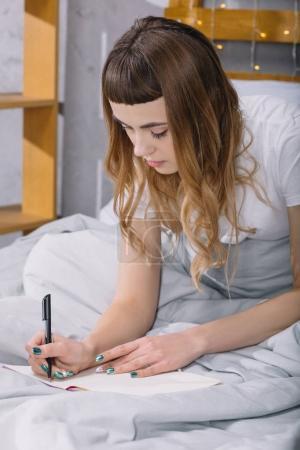 Foto de Chica escribir algo para el notebook en la cama en la mañana - Imagen libre de derechos