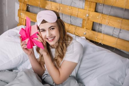 happy girl sitting in bed and listening what inside present box