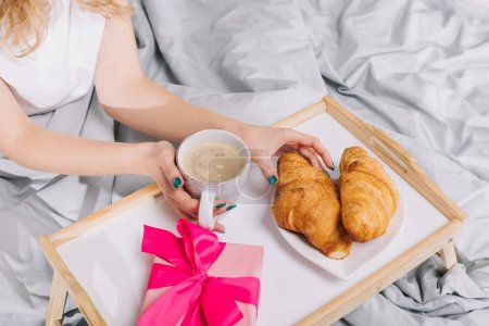 cropped image of girl taking croissant from plate