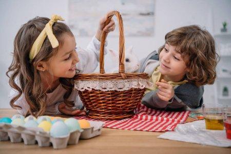 Photo pour Heureux petits enfants jouer avec mignon lapin dans panier sur la table avec des œufs de Pâques - image libre de droit