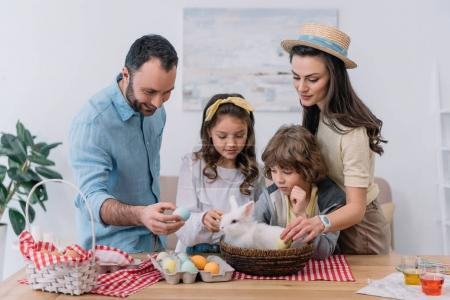 young family preparing for easter holiday with bunny sitting in basket on table