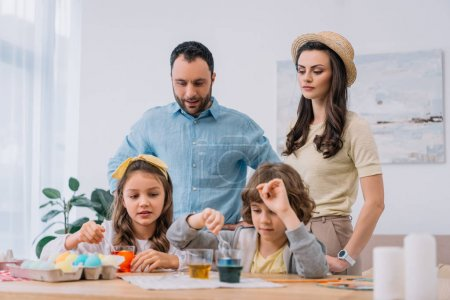 young family painting eggs for easter holiday at home