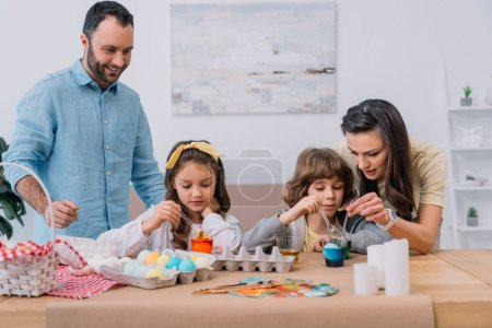 beautiful young family painting eggs for easter at home