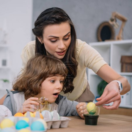 Photo pour Fils d'aider la mère avec des oeufs de peinture pour les vacances de Pâques - image libre de droit
