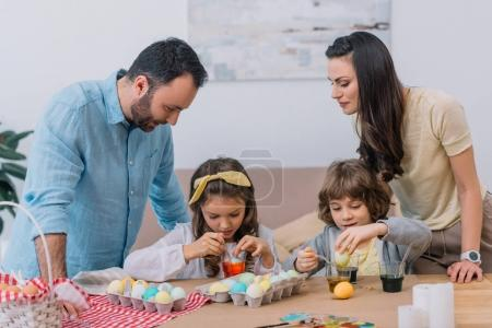 happy young family painting eggs for easter at home
