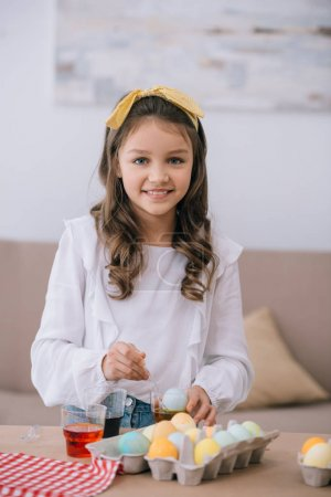 smiling little child painting easter eggs and looking at camera