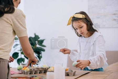 concentrated little daughter painting easter eggs together with mother
