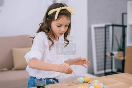 focused little child painting easter eggs