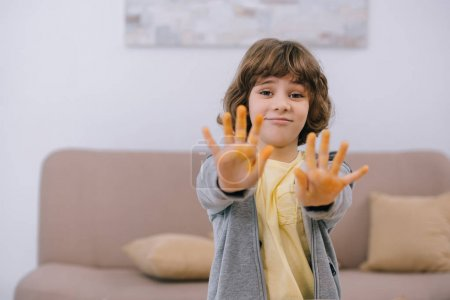 happy kid showing dirty hands painted in yellow