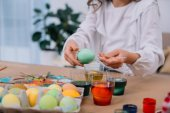 cropped shot of child painting easter eggs