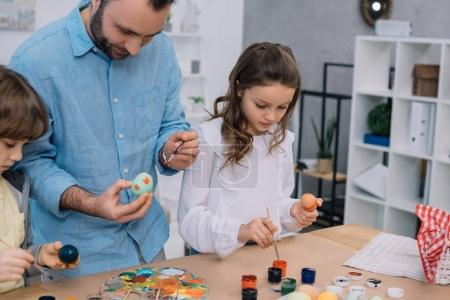father and children painting eggs for easter holiday
