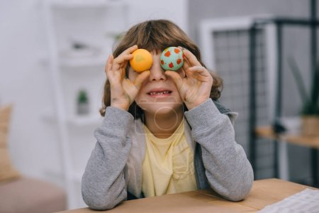 little kid covering eyes with easter eggs