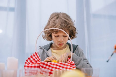 sad little kid looking at basket with red napkin