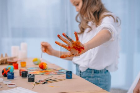 little child showing colorful dirt hand while painting eggs