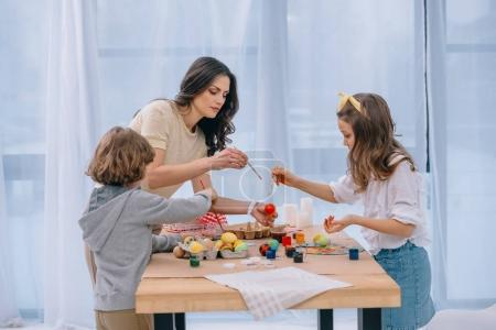adorable children painting easter eggs mother at home with mother