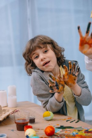 little kid showing his dirty colorful hands at camera