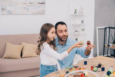 Photo pour Père avec fille regardant des oeufs de Pâques fraîchement peints - image libre de droit