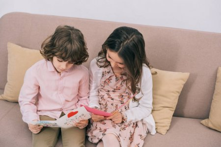 children with mothers day greeting cards sitting on couch at home