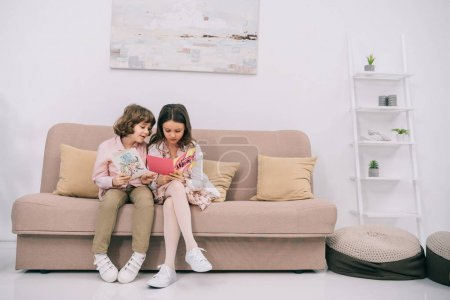 kids with mothers day greeting cards sitting on couch