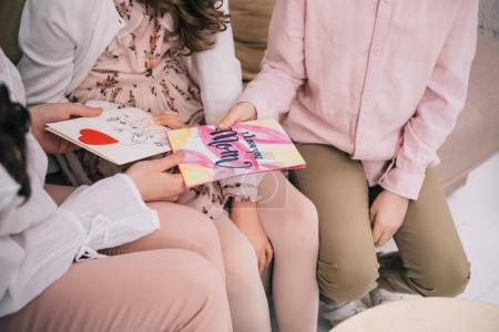 cropped shot of kids sitting with mother on sofa and showing her greeting cards for mothers day