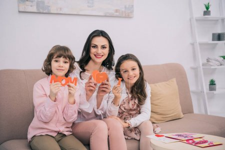 kids sitting on cozy couch with mother