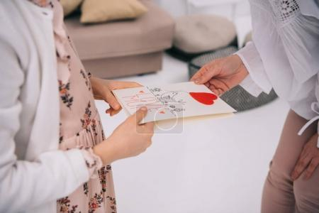 Photo for Cropped shot of daughter presenting greeting card for mother - Royalty Free Image