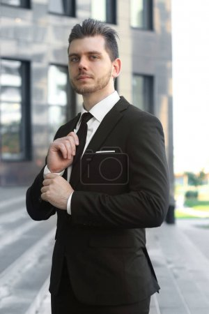 businessman adjusting his tie at the entrance to the office building