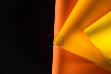 orange and yellow papers isolated on black