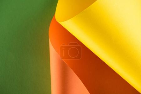 rolled yellow and orange papers on green background