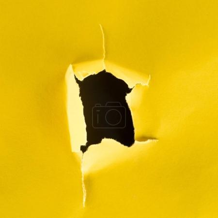 Photo for Close-up shot of hole in yellow paper isolated on black - Royalty Free Image