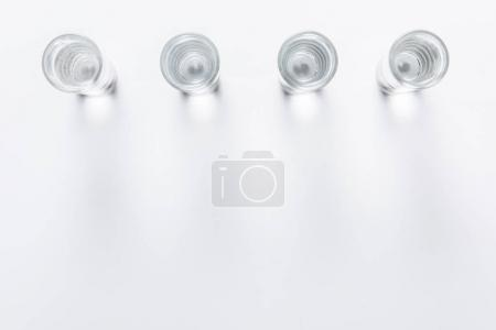top view of row of small glasses with water on white table