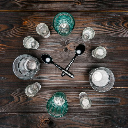 top view of circle with different sized glasses with water and spoons on wooden table