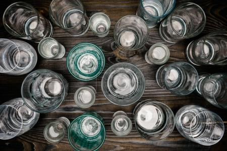 top view of different sized glasses with water on wooden table