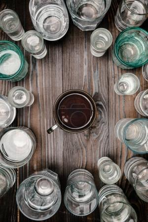 top view of cup of tea between glasses with water on wooden table