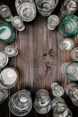 top view of glasses with water on wooden table