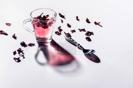 Photo for Glass cup of hibiscus tea with spoon and scattered tea on table - Royalty Free Image
