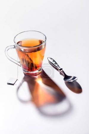 Photo for Glass cup of black tea and spoon on table - Royalty Free Image