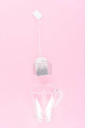 Photo for Top view of one tea bag and empty glass cup isolated on pink - Royalty Free Image