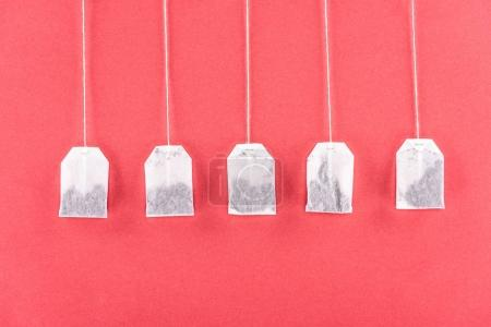 Photo for Top view of five unused tea bags isolated on red - Royalty Free Image