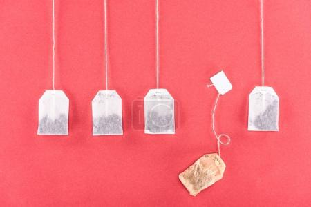 top view of four unused tea bags and one used tea bag isolated on red